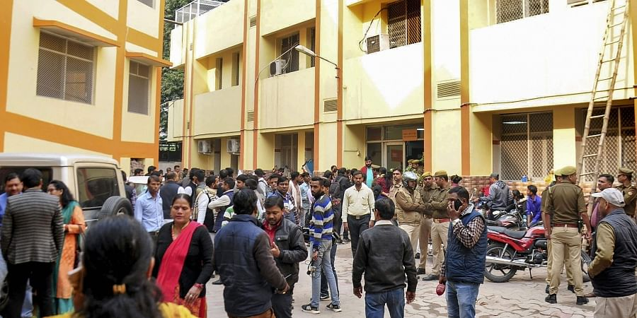 People stand outside the Shyama Prasad Mookerjee Civil Hospital where the Unnao rape survivor is currently undergoing treatment after being set ablaze by five men at Sindupur village in Unnao district in Lucknow Thursday Dec. 5 2019. (Photo | PTI)