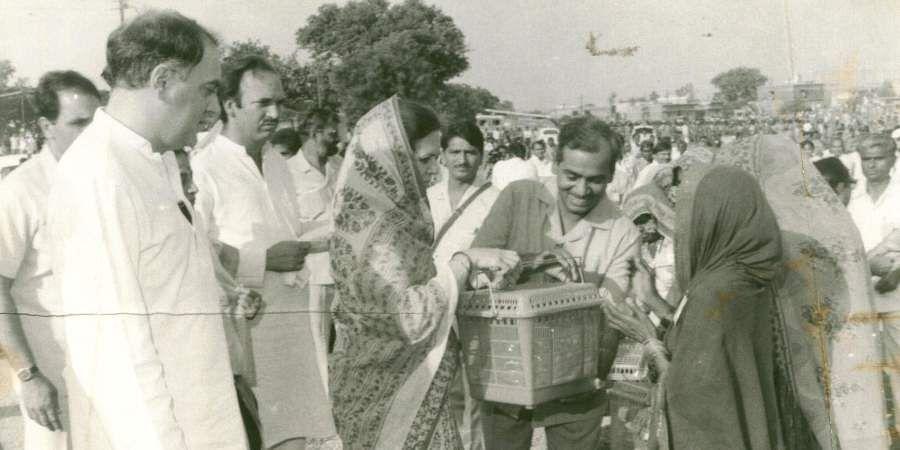 Sonia Gandhi distributing utensils to some Banjara women. Then PM Rajiv Gandhi is also seen.