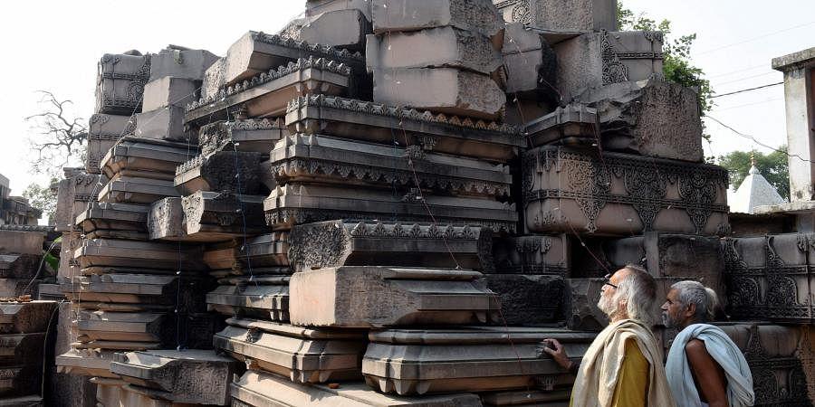 Visitors look at stone slabs carved-out for the construction of Ram Temple at Shri Ram Janmbhoomi Karyashala workshop in Karsewakpuram Ayodhya (Photo | PTI)