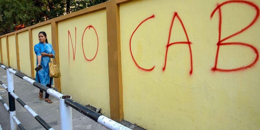 A pedestrain walks past a wall graffiti opposing the Citizenship Amendment Bill CAB in Guwahati Monday Dec. 9 2019. (Photo | PTI)
