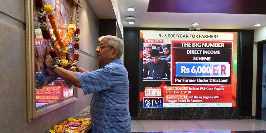 A broker offers prayers as the announcement of the interim Union Budget by Finance Minister Piyush Goyal plays on a screen. (Photo | PTI)