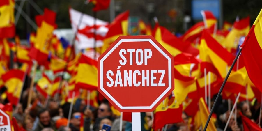 Demonstrators hold banners and Spanish flags during a protest in Madrid, Spain. (Photo | AP)