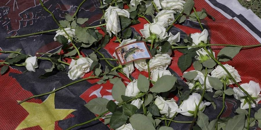 Roses and an image of Saint Judas Tadeus placed by fans are displayed over a Flamengo's flag