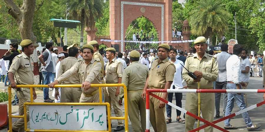 Security personnel stand guard as Aligarh Muslim University students stage a protest over Jinnah portrait issue outside the university gate in Aligarh on Friday, 04 May 2018.   PTI