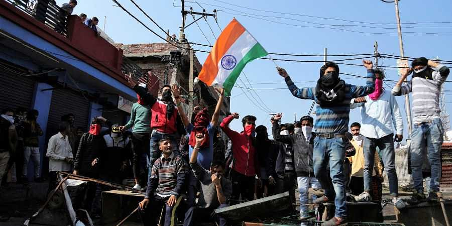 Indian protestors shout slogans against Pakistan during the second day of curfew in Jammu.