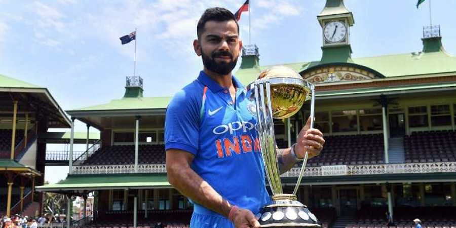 Virat Kohli poses with the ICC Cricket World Cup trophy. (Photo   AFP)