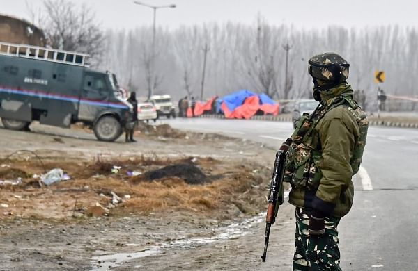 A security personnel stands guard at the site of suicide bomb attack at Lethpora area in Pulwama district of south Kashmir Friday Feb. 15 2019. | PTI