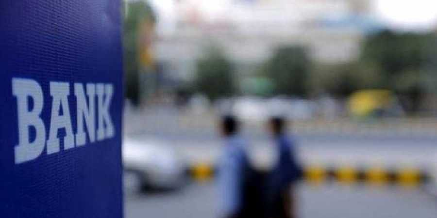 Commuters walk past a bank sign along a road in New Delhi (Photo | Reuters)