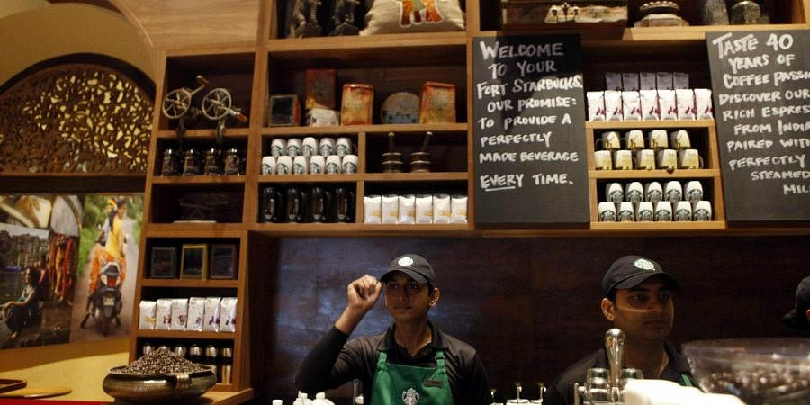 Employees at the first India outlet of Starbucks work at a counter in Mumbai. (Photo| AP)