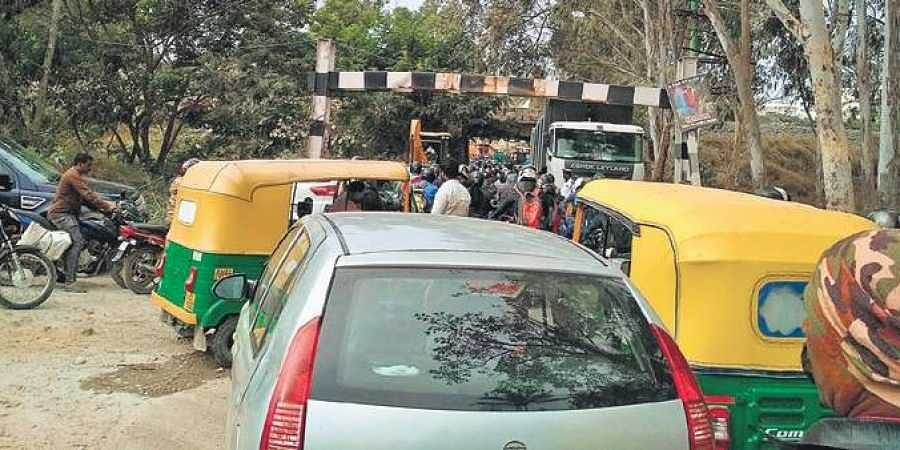 Vehicles line up on one side of the road on Balagere-Panathur road.