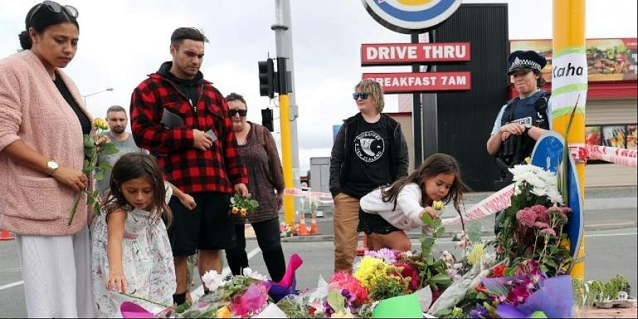 Residents place flowers at the police cordon as police conintue to search the area close by the Linwood Ave Mosque in Christchurch. (Photo | AFP)