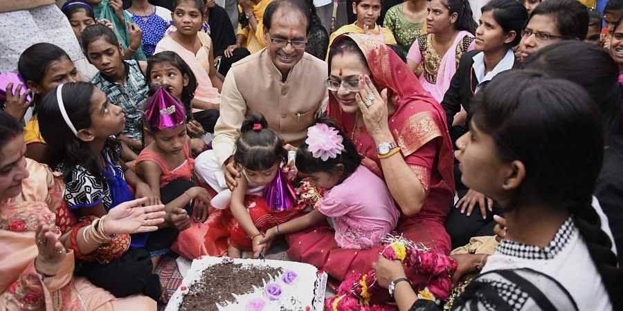Madhya Pradesh Chief Minister Shivraj Singh Chouhan celebrates his birthday with his wife Sadhna Singh and orphan children of Bal Niketan in Bhopal.   PTI