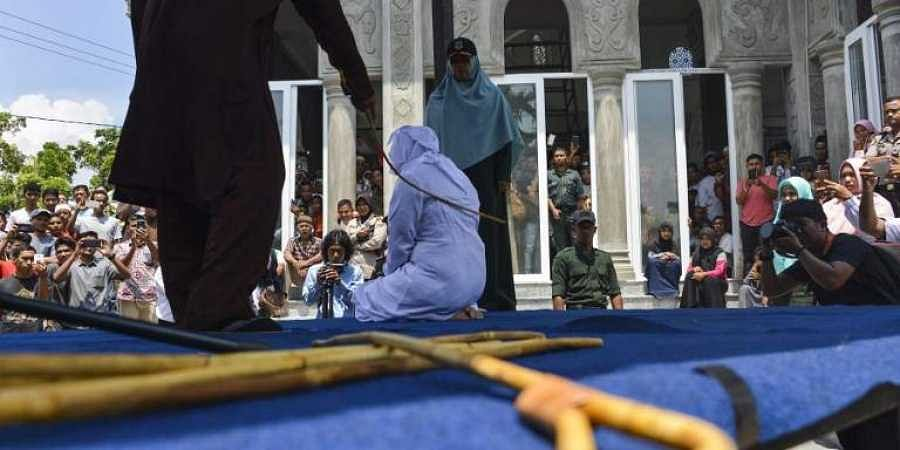 People watch as an Indonesian woman is whipped by a member of the Sharia police in public in Banda Aceh. (Photo | AFP)