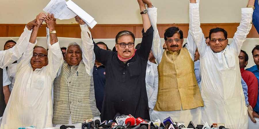 RJD MP Manoj Jha, state's party President Ramchandra Purbey and Congress' state president Madan Mohan Jha join hands after announcing the grand alliance's candidates list for the upcoming Lok Sabha elections in Patna on 22 March 2019. (Photo | PTI)