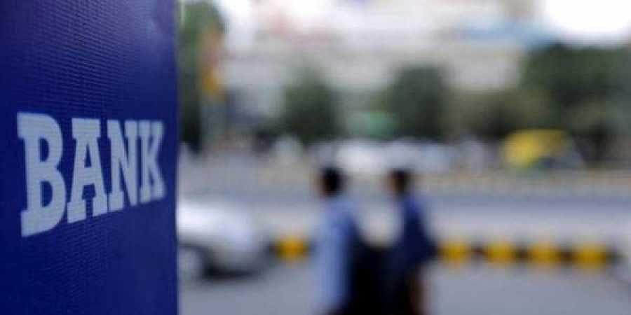 Commuters walk past a bank sign along a road in New Delhi (Photo | Reuters)