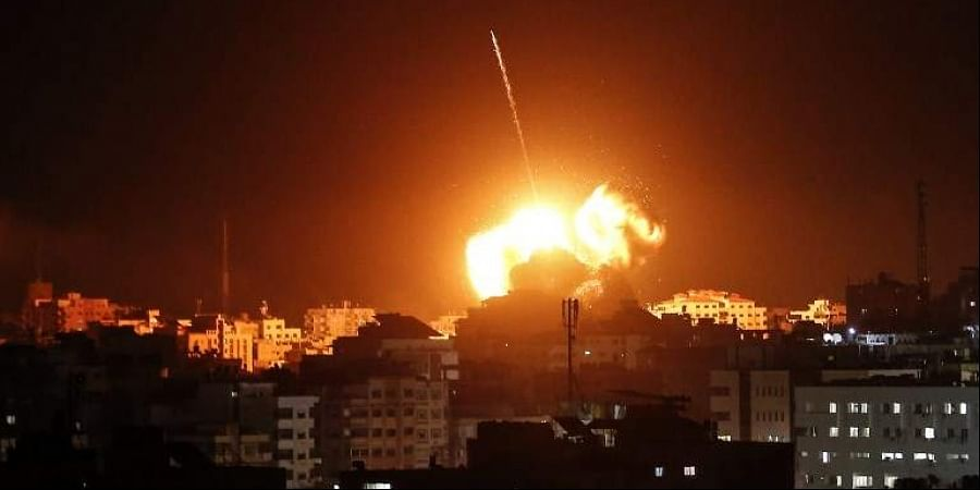 A ball of fire lights the sky above a building believed to house the offices of Hamas chief in Gaza, Ismail Haniyeh, during Israeli strikes on the Gaza City