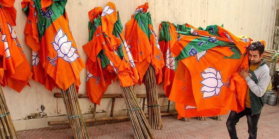 A worker carries Bharatiya Janata Party flags for distribution ahead of an election campaign in Jammu. (Photo | PTI)