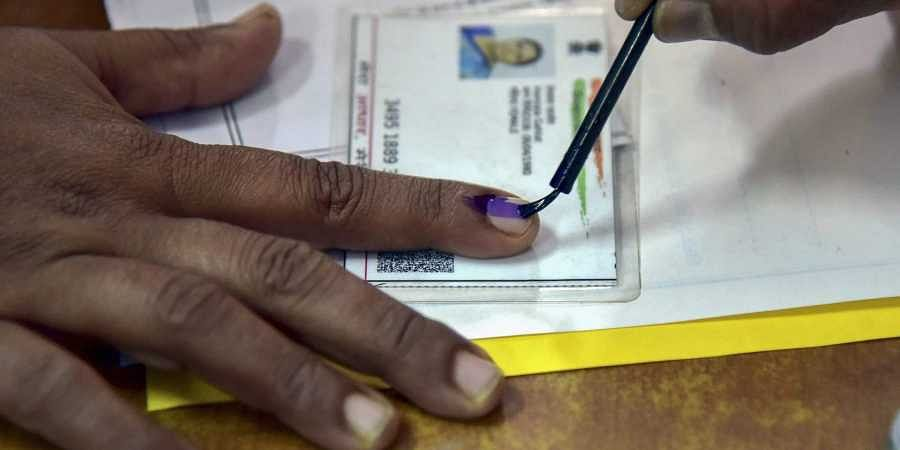 An election officer put an indelible ink mark on the finger of a voter during the state Assembly elections in Bikaner. (Photo | PTI)
