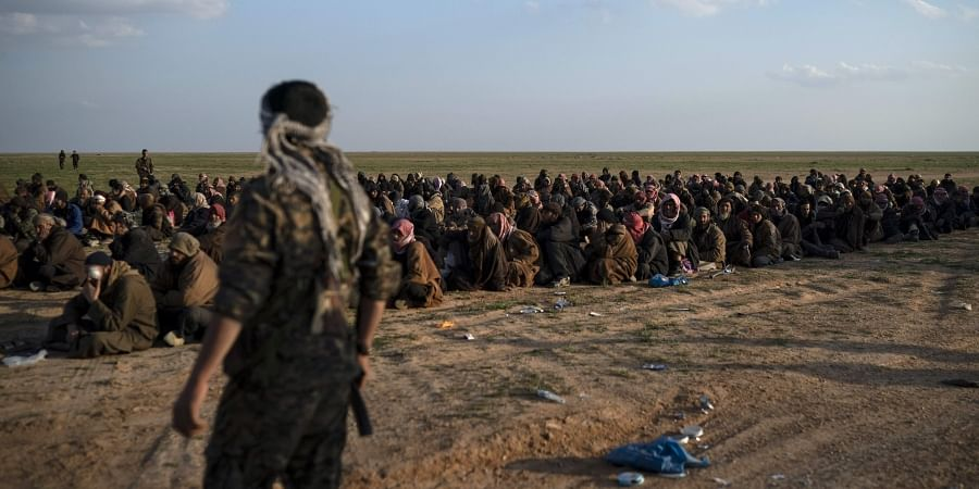 FILE - In this Friday, Feb. 22, 2019 file photo, U.S.-backed Syrian Democratic Forces (SDF) fighters stand guard next to men waiting to be screened after being evacuated out of the last territory held by Islamic State group militants, near Baghouz, eastern Syria. (Photo   AP)