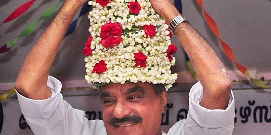 An overjoyed KM Mani as finance minister adjusts a flower crown which was presented to him as he arrived to inaugurate the State convention of the Kerala State Stamp Vendor's Association at Thiruvananthapuram on Tuesday