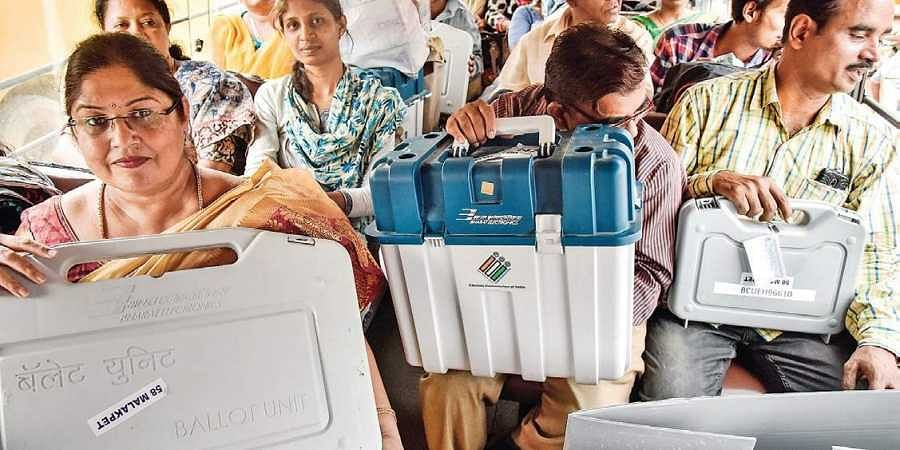 Polling staff take EVM and VVPAT machines from LB Stadium  in Hyderabad on Wednesday