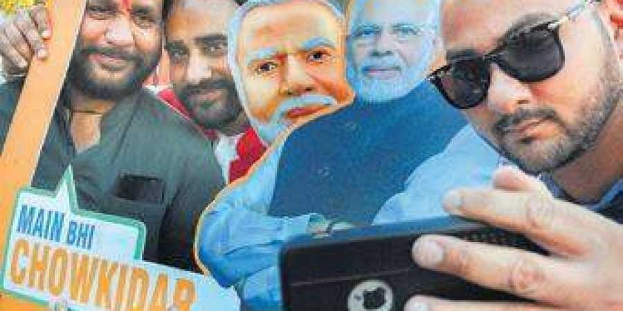 Supporters take selfies with a picture of PM as they take part in an event of 'Main Bhi Chowkidar' campaign