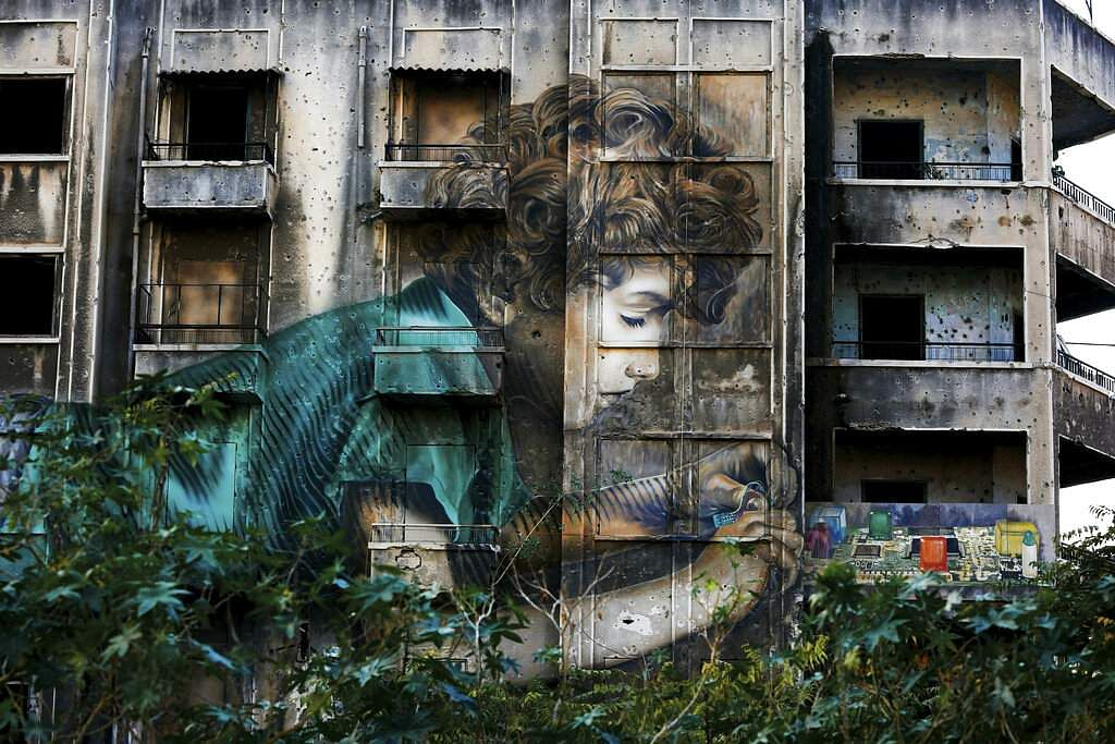 In this Nov. 12, 2018, photo, graffiti by Cuban-American artist Jorge Rodriguez-Gerada depicting a boy is painted on a bullet riddled building on the former frontline of the 1975-1990 Lebanese civil war in downtown Beirut, Lebanon.