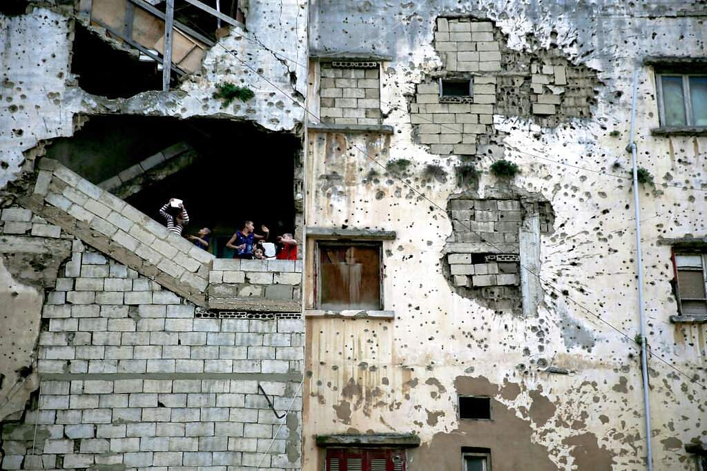 In this Nov. 28, 2015, photo, Syrian refugee children stand on the stairs of their apartment in a building damaged during Lebanon's 1975-1990 civil war on a former Beirut frontline, Lebanon.