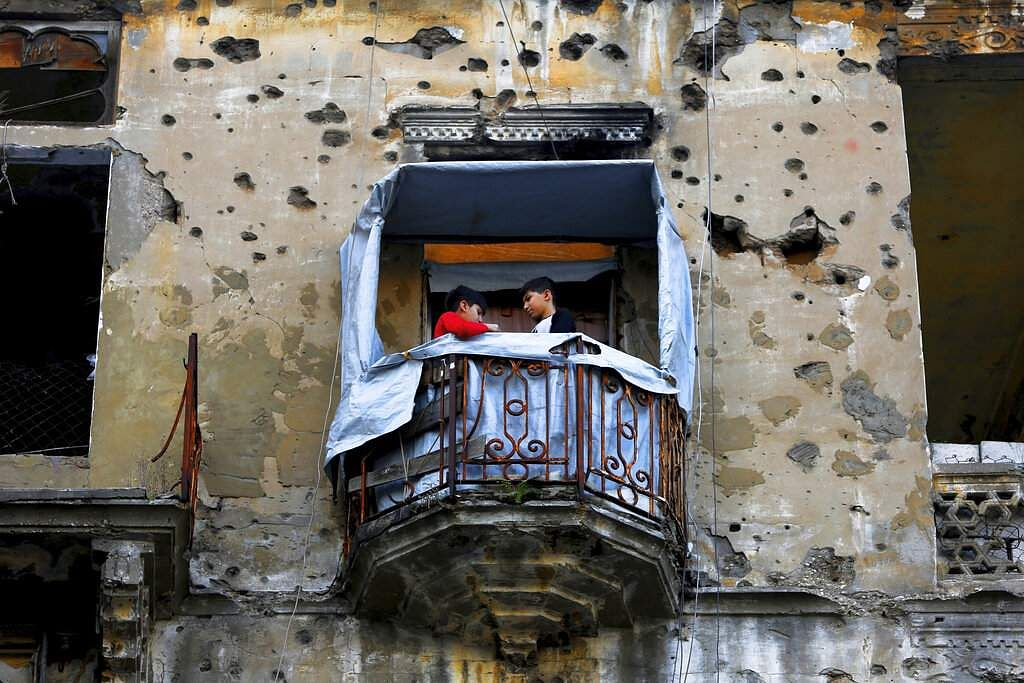 In this Nov. 12, 2018, photo, children stand on the balcony of their apartment building damaged during Lebanon's 1975-1990 civil war on a former Beirut frontline, Lebanon.
