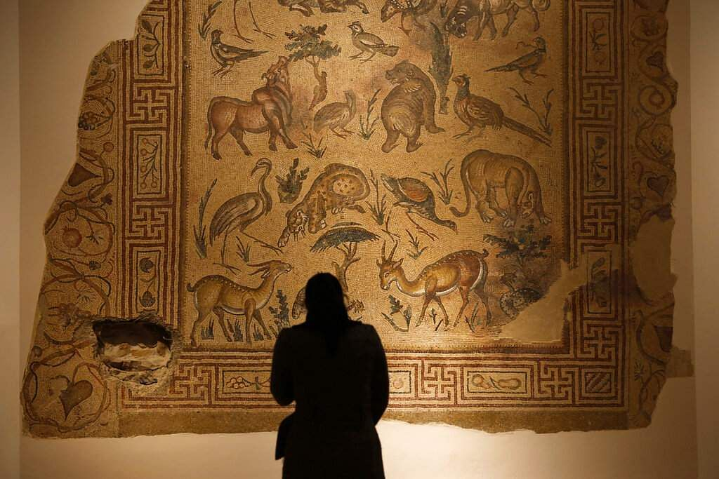 In this Jan. 28, 2016, photo, a visitor checks the mosaic of the Good Shepherd that was badly damaged in the lower left corner by a sniper during the 1975-1990 Lebanese civil war at the Lebanese National Museum in Beirut, Lebanon.