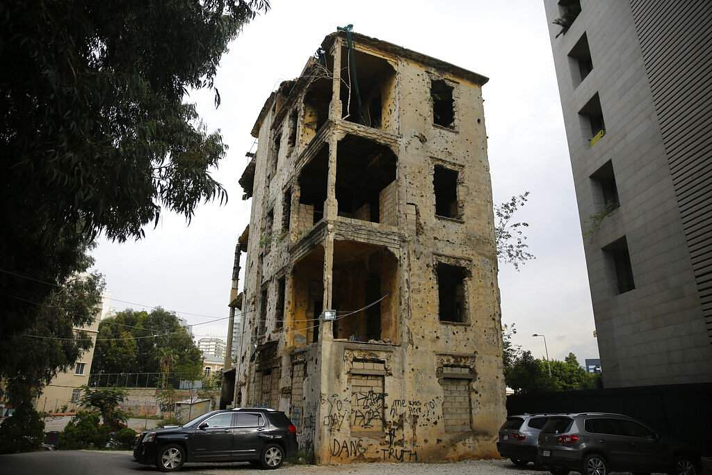 In this Dec. 2, 2018, photo, cars park in front of a building that is still riddled with bullets and shells on the former frontline of the 1975-1990 Lebanese civil war in Beirut, Lebanon.
