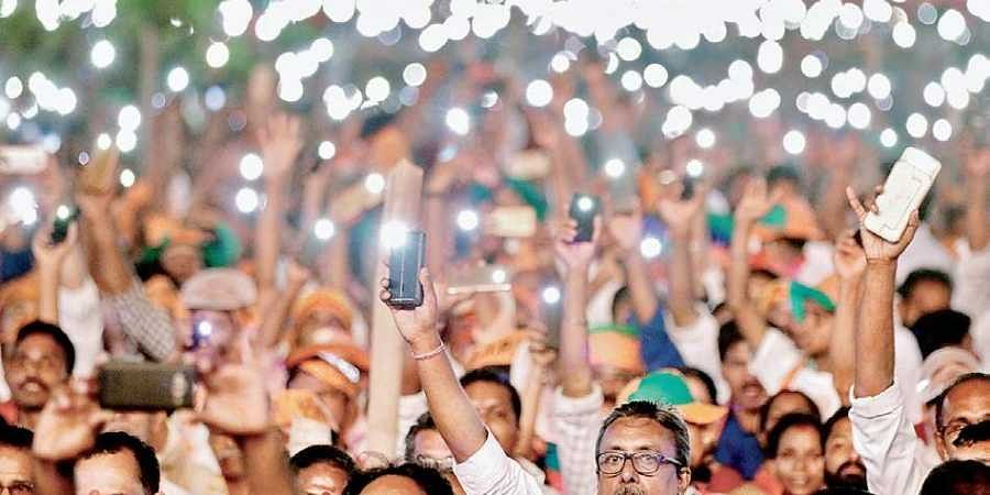 BJP workers turn on  the flash lights on their mobile phones to welcome Prime Minister Narendra Modi at the Vijay Sankalp rally on Kozhikode beach on Friday