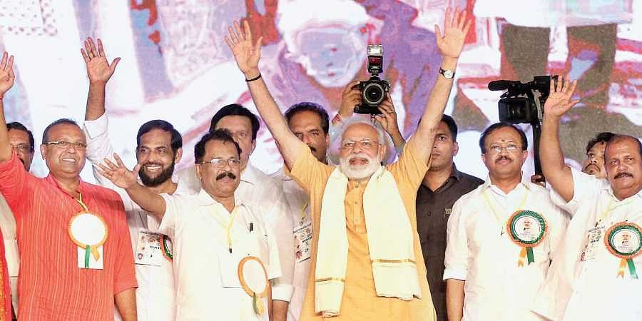Prime Minister Narendra Modi waving at party workers during the Vijay Sankalp rally on Kozhikode beach on Friday