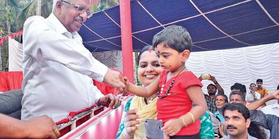 P Jayarajan, LDF Vadakara candidate, shakes hands with a toddler while campaigning for polls at Purameri in Vadakara