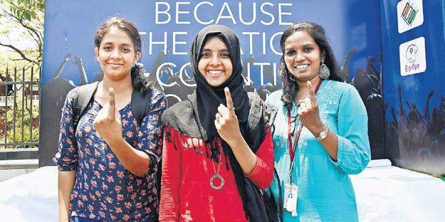 Youngsters pose in front of the TNIE election awareness campaign float at Kamarajar Salai