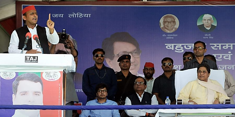 Samajwadi Party President Akhilesh Yadav addresses as Bahujan Samaj Party supremo Mayawati is seen on the stage during their joint election campaign rally in Badaun. (Photo | PTI)