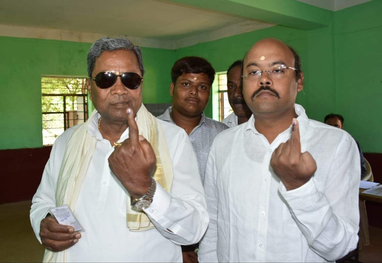 Former CM Siddaramaiah and his son MLA Yathindra exercised their franchise at a polling station in Siddaramanahundi in Mysuru. (Photo | Udayshankar S, EPS)