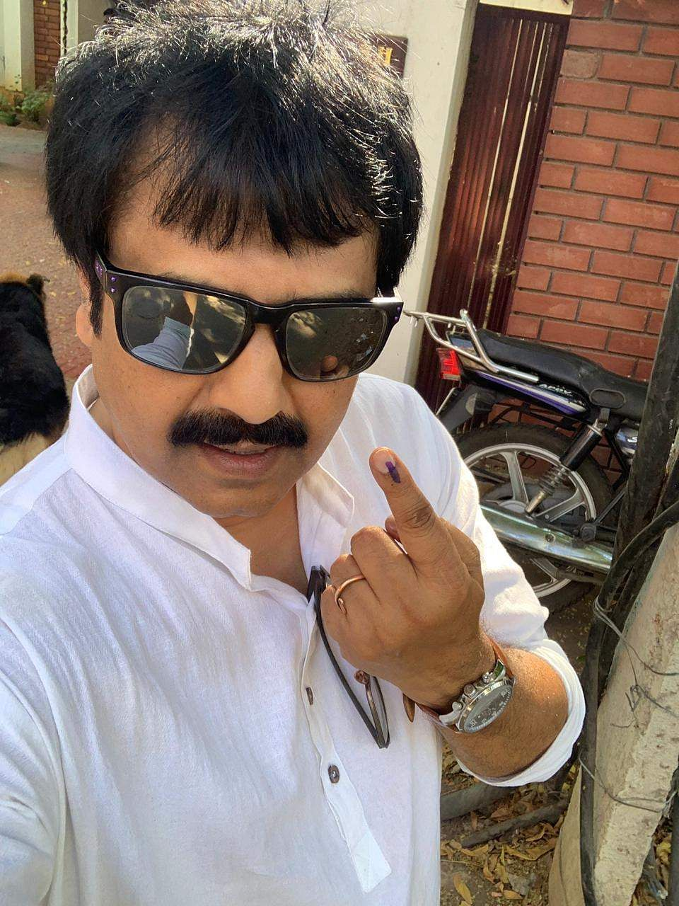 Tamil actor and comedian Vivekh takes a photo after voting.