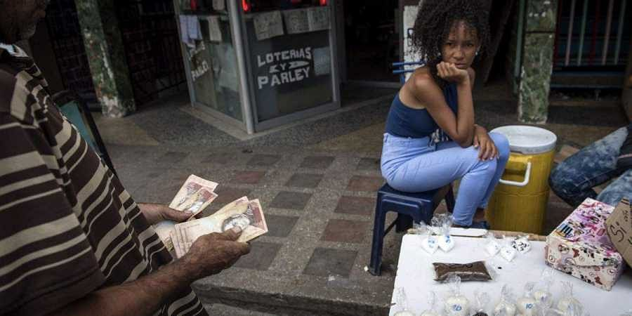 A customer counts Bolivar banknotes before purchasing coffee and sugar in the Petare slum of Caracas. (Photo | Bloomberg)