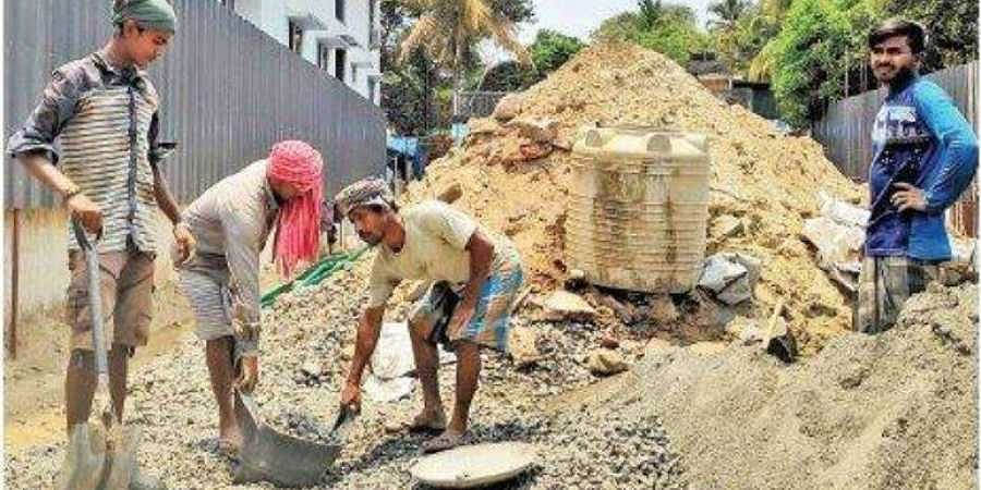 Migrant labourers busy with their work at 1 pm in a construction site in Kaloor.
