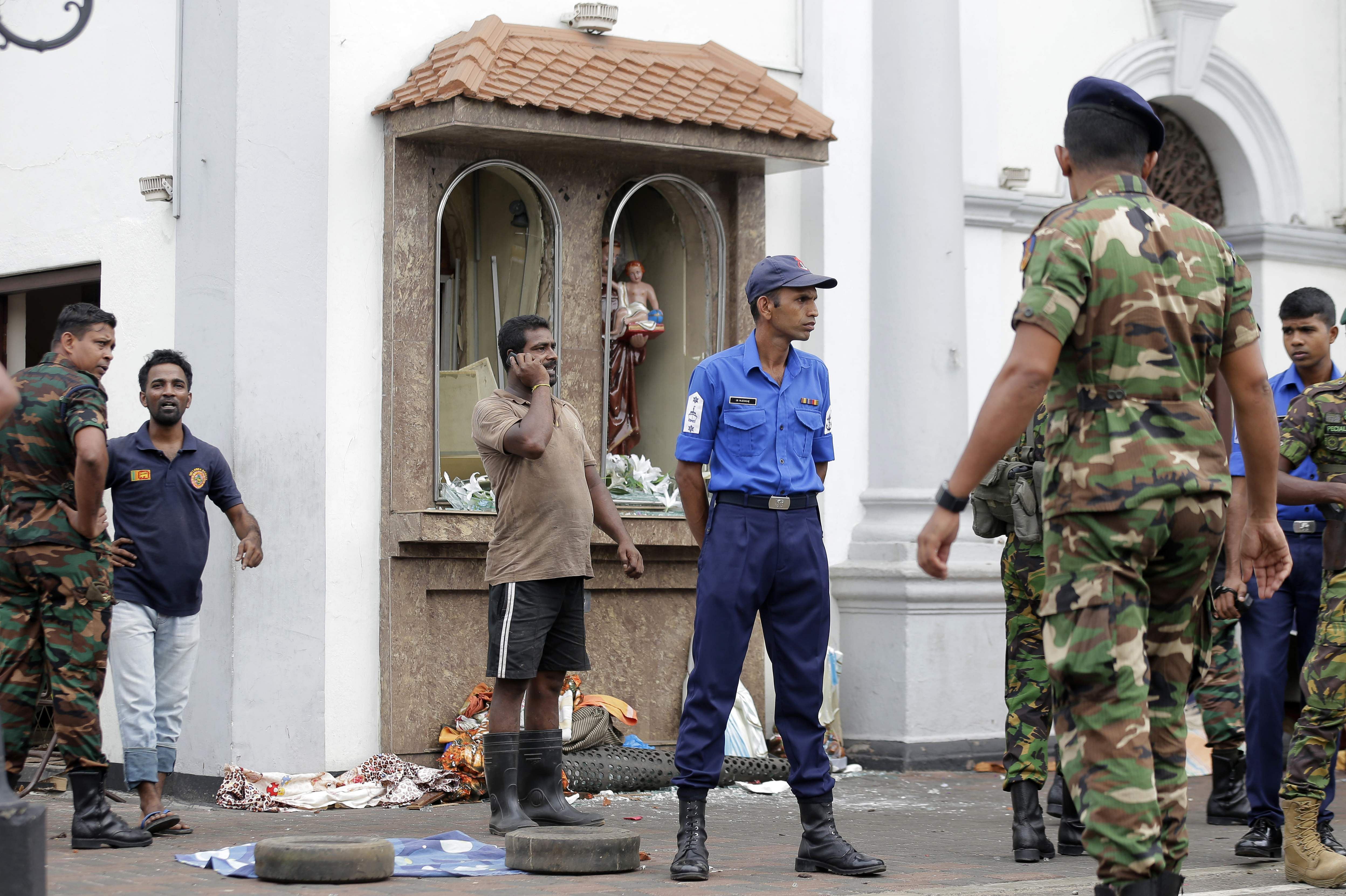 People gather outside St. Anthony's Shrine where a blast happened, in Colombo, Sri Lanka.