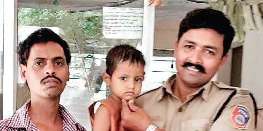 A fireman holds Divya, the four-year-old rescued girl, on Sunday | Express
