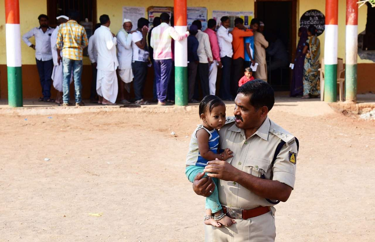 A police officer takes care of a child while the mother waits in a queue for polling at Ainapur village near Vijayapura, Karnataka. (Photo | Vinod Kumar T, EPS)