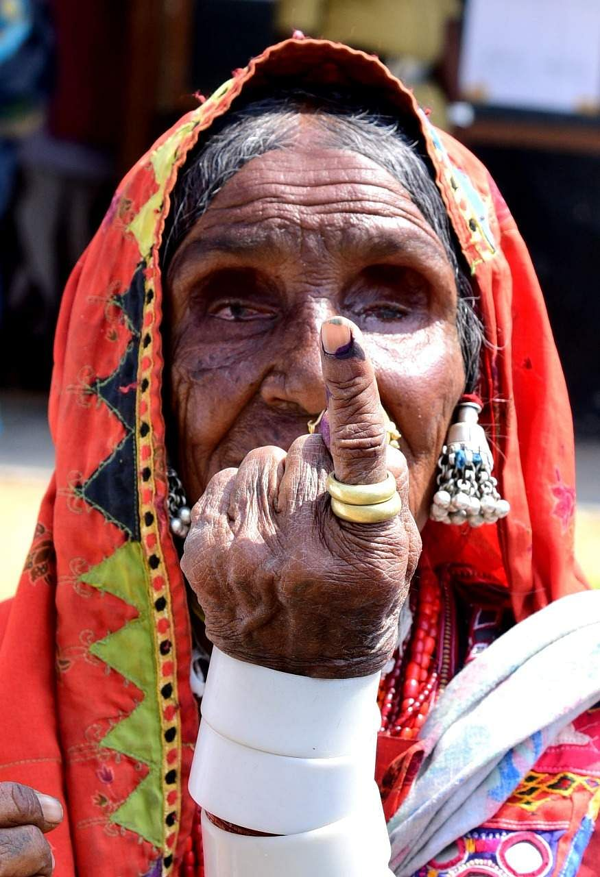 A tribal woman shows her inked finger after voting in Karnataka. (Photo | Vinod Kumar T, EPS)