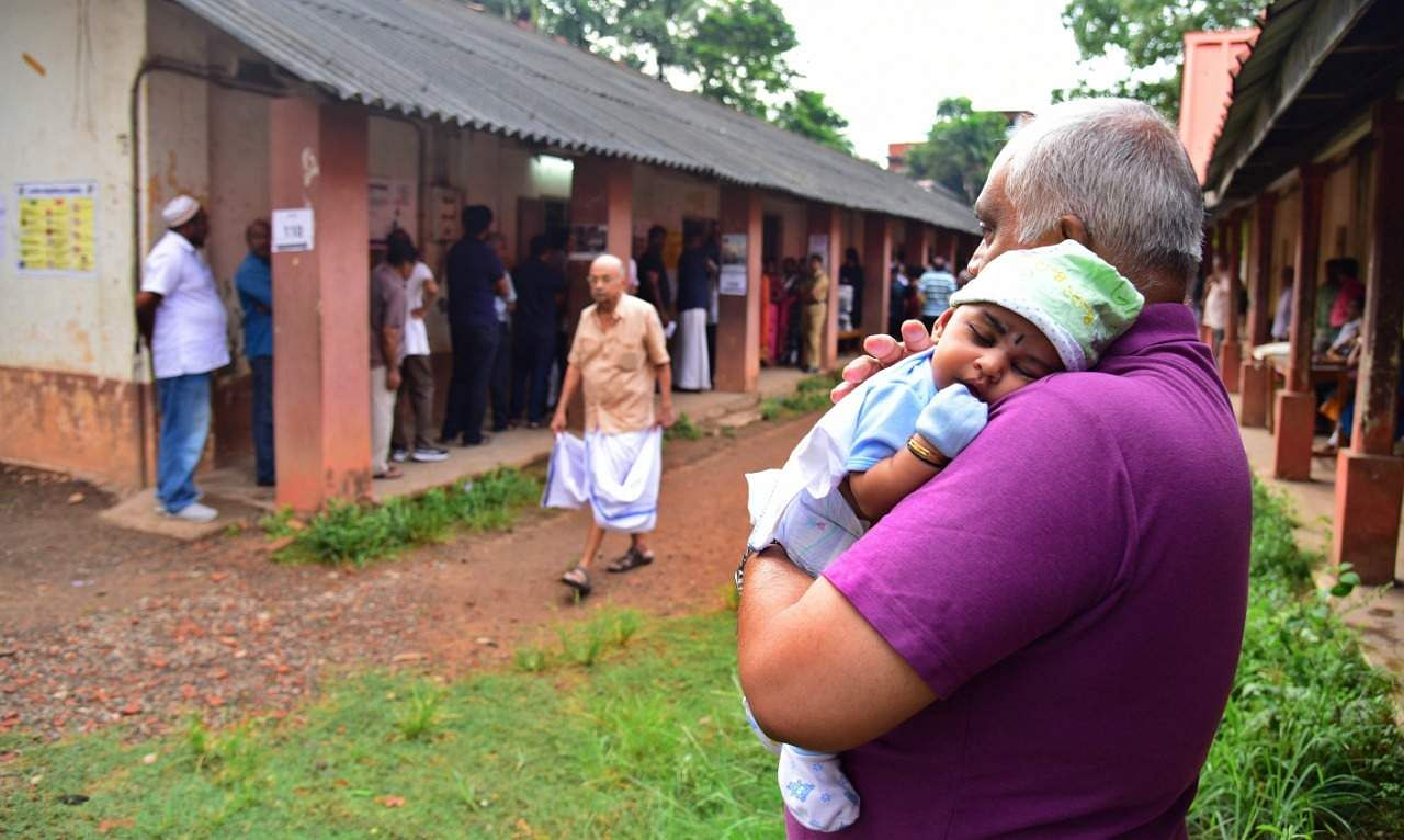 An elderly man holds his grandchild while waiting outside Technical Higher Secondary School Kaloor in Kochi after casting his vote. (Photo | Albin Mathew, EPS)