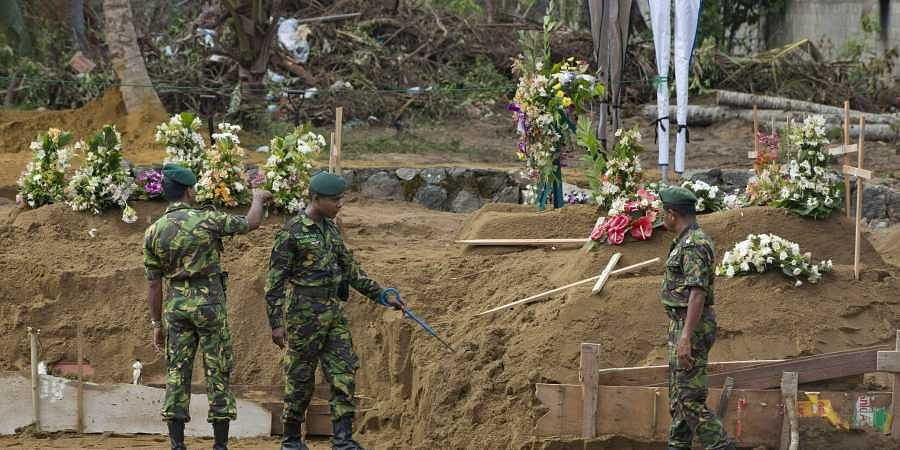 Officers of Special Task Force search for explosives ahead of mass burials at a burial ground in Sri Lanka