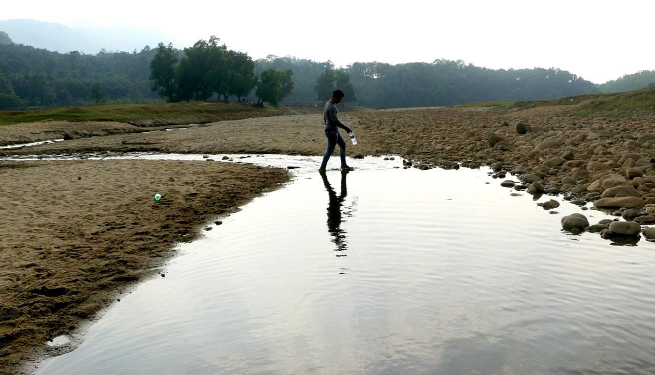 With mercury level rising, water bodies in Kozhikode have started drying up. A boy crossing the nearly-dried-up Kadatharappuzha river with a bottle of water, in Kozhikode. (Photo | T P Sooraj)