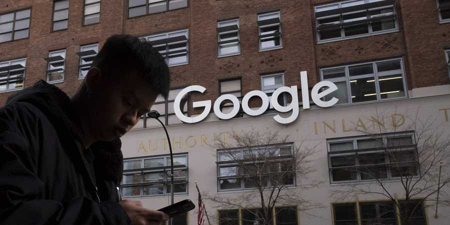 A man using a mobile phone walks past Google offices in New York. Google says it plans to launch a video-game streaming platform called Stadia, positioning itself to take on the traditional video-game business