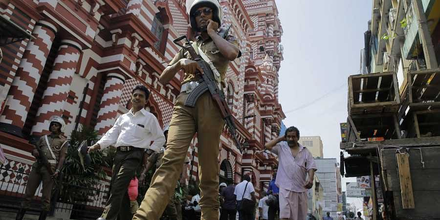 A Sri Lankan police officer patrols out side a mosque in Colombo