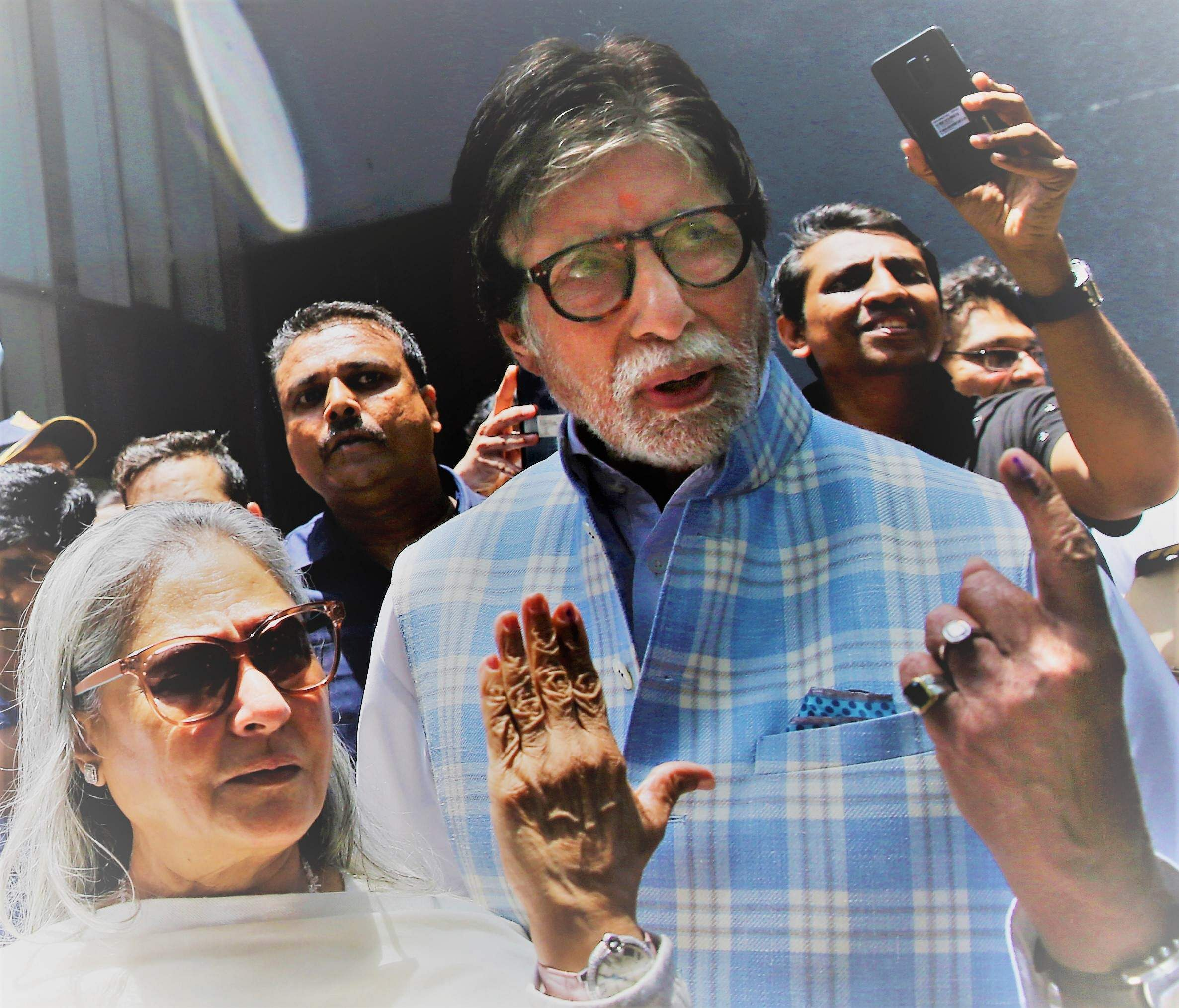Bollywood star Amitabh Bachchan, right along with his wife Jaya Bachchan, poses for the media after casting their vote at a polling station in Mumbai.
